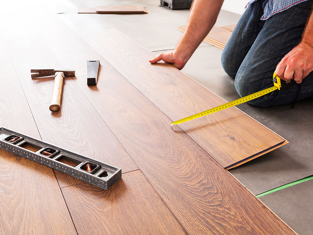 Worker measuring laminate floor with measuring tape and level