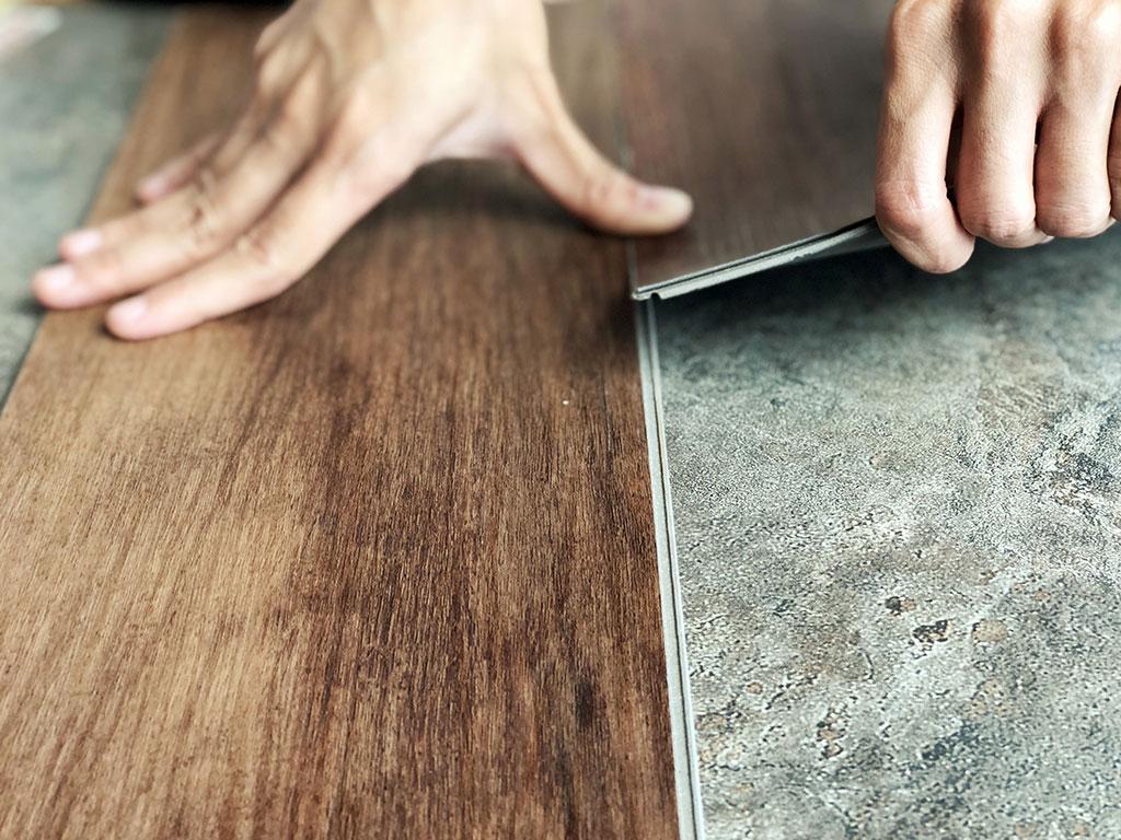 Hands laying down laminate flooring