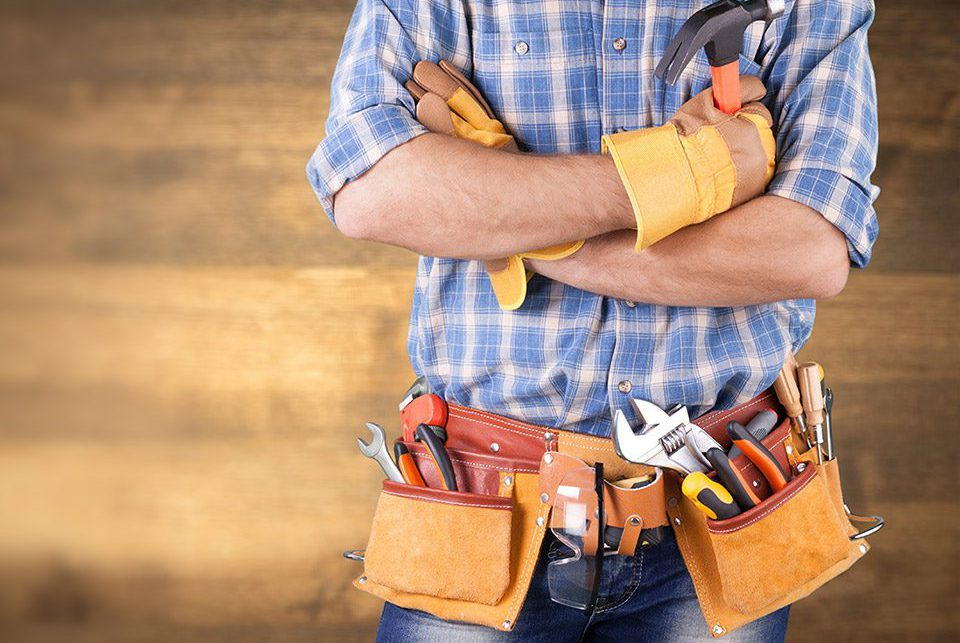 Man standing with tool belt full of tools in front of woodgrain background